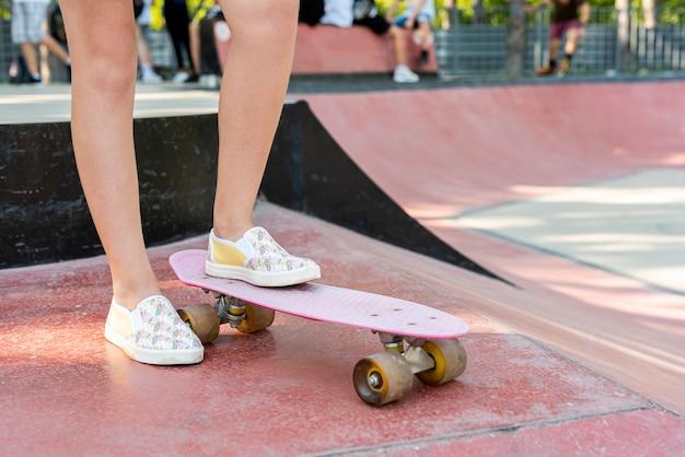 Primer plano de zapatos en patineta rosa Foto gratis