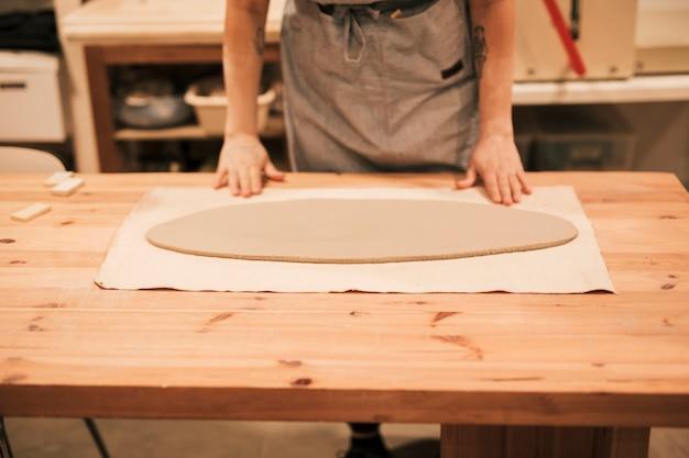 El primer del potter femenino con forma oval aplana la arcilla en la tabla de madera Foto gratis