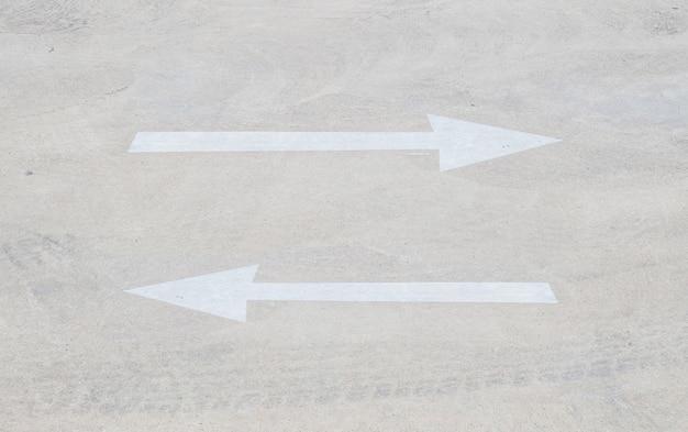Primer signo de flecha pálida en el piso de cemento en el aparcamiento Foto Premium