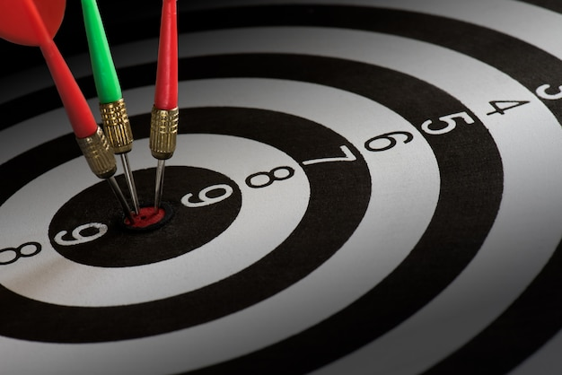 El primer tiró flechas rojas y verdes del dardo en el centro de la diana, concepto del éxito de la blanco. Foto Premium