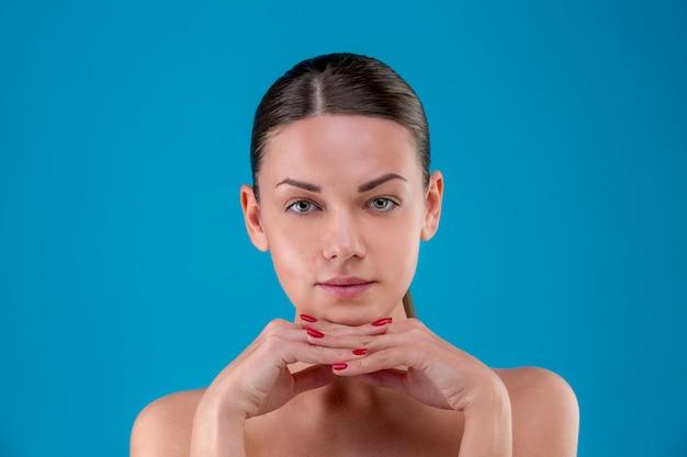 Primeros labios y hombros de la mujer caucásica joven con maquillaje natural, piel perfecta y ojos azules aislados en azul. retrato de estudio Foto Premium