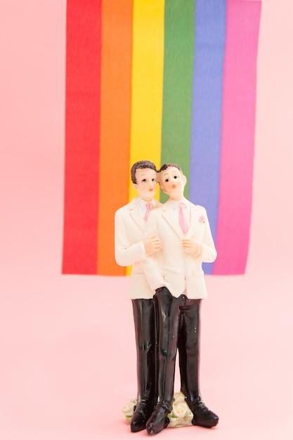 Primeros de la torta del novio gay delante de la bandera del arco iris Foto Premium