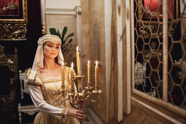 Princesa en ropa de oro lleva candelabro con velas encendidas Foto Gratis