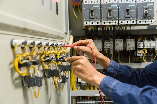 Probador de electricista que mide la tensión y la corriente en el control  del gabinete eléctrico | Foto Premium