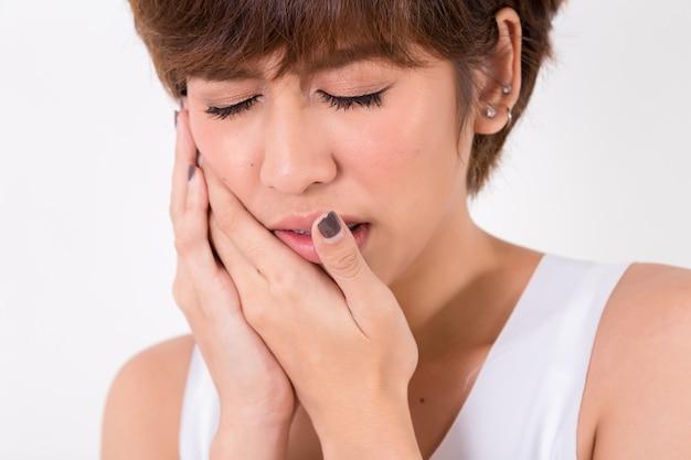 Problema de los dientes. mujer siente dolor de dientes. aislado en blanco estudio de iluminación. concepto de salud y medicina. Foto Premium