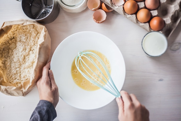 Proceso de hacer la masa, la mano de la mujer bate los huevos y la harina en un tazón. Foto Premium