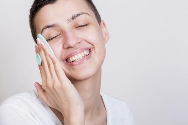 Proceso de limpieza de cara de mujer sonriente Foto gratis