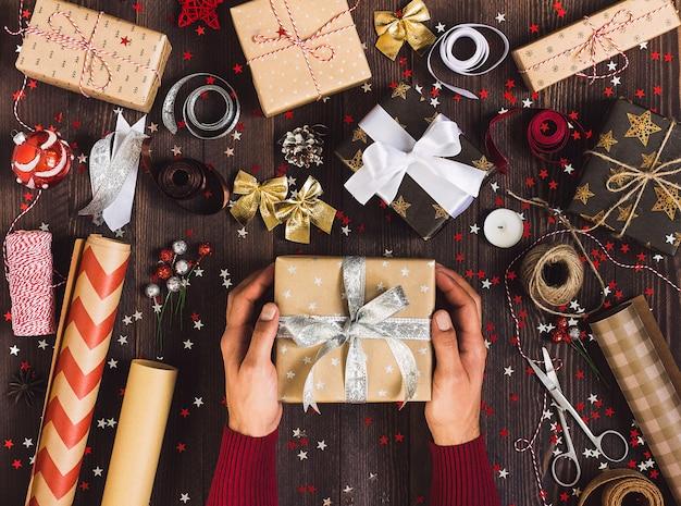 Proceso del paquete caja de regalo de navidad hombre en mano sosteniendo la caja de regalo de año nuevo Foto gratis