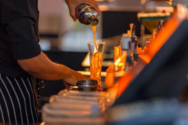Proceso de preparación de un cóctel de camareros a partir de maracuyá Foto Premium