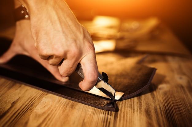 Proceso de trabajo del cinturón de cuero en el taller de cuero. herramienta de sujeción de hombre. curtidor en la antigua curtiduría. superficie de la mesa de madera. ciérrese encima del brazo del hombre. luz cálida para texto y diseño. tamaño de banner web Foto Premium