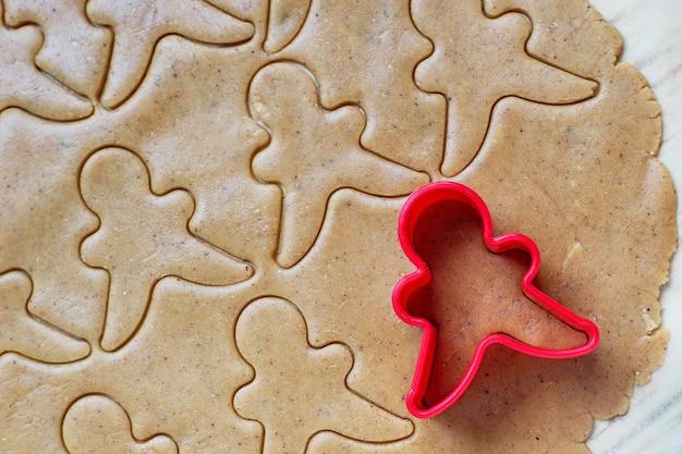 Proceso de tratar con las galletas de hombre de pan de jengibre, use molde de hombre de pan de jengibre rojo para cortar masa de pan de jengibre sobre papel de hornear alrededor de coloridos cortadores de galletas en la mesa de madera blanca. vista superior Foto gratis