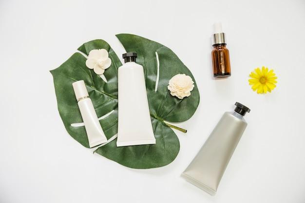 Producto cosmético y flor en monstera hoja y botella de aceite esencial sobre fondo blanco Foto gratis