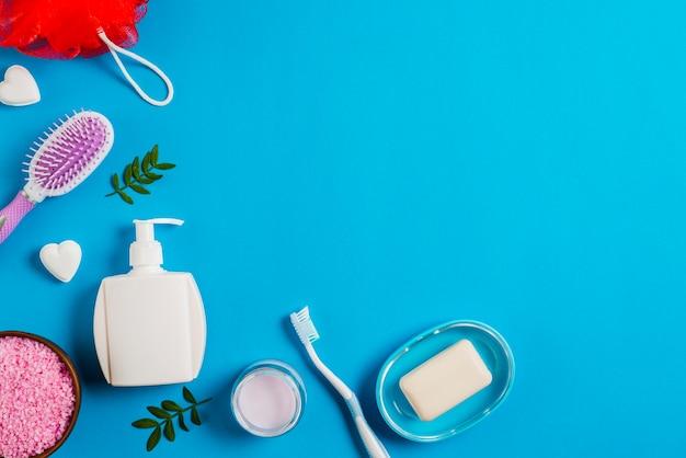 Productos de baño con sal; cepillo de dientes; esponja y cepillo sobre fondo azul Foto gratis