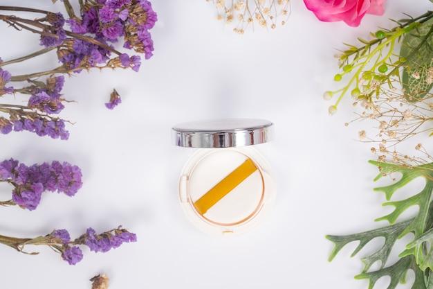 Productos cosméticos y flores en blanco Foto gratis