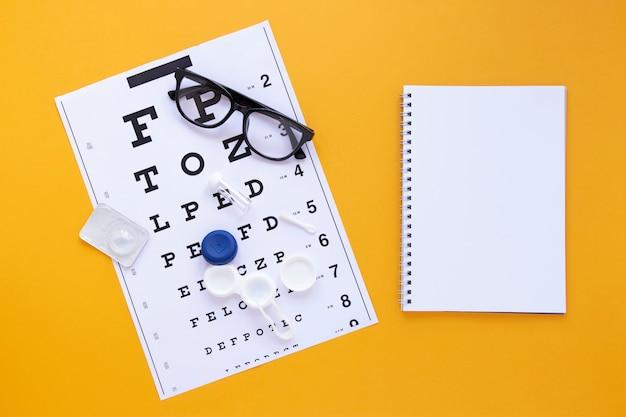 Productos para el cuidado de los ojos con maqueta de cuaderno sobre fondo naranja Foto gratis