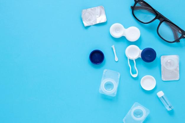Productos para el cuidado de los ojos sobre fondo azul con espacio de copia Foto gratis