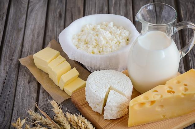 Productos lácteos frescos. leche, queso, mantequilla y requesón con trigo en el fondo de madera rústica. Foto Premium