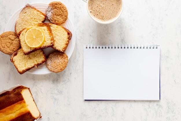 Productos de pastelería cerca de un cuaderno Foto gratis