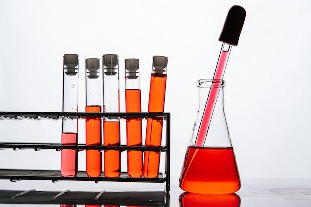 Productos químicos de color naranja en un tubo de vidrio de ciencia dispuestos en un estante Foto gratis