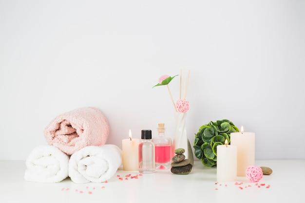 Productos de spa y velas iluminadas sobre tablero blanco. Foto gratis