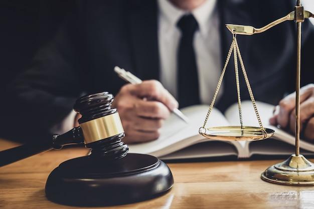 Profesional abogado o juez de sexo masculino que trabaja con documentos contractuales, documentos y medidas y escalas de la justicia en la sala de audiencias, concepto de servicios legales y legales Foto Premium