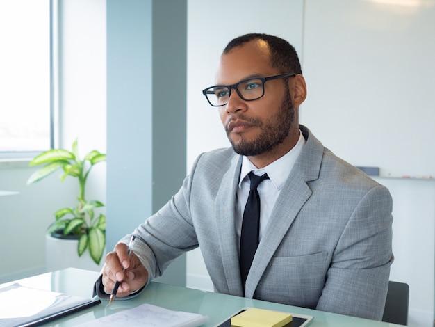Profesional de negocios enfocado escuchando al orador Foto gratis