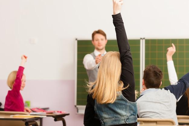 Profesor con alumno en la enseñanza escolar Foto Premium