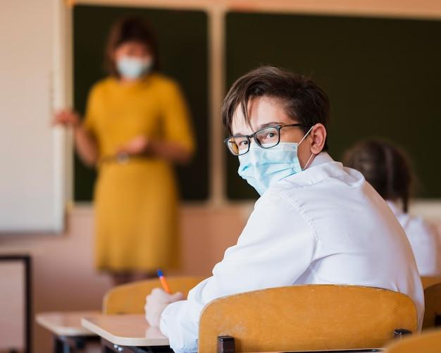 Profesor y alumnos con máscara. Foto gratis