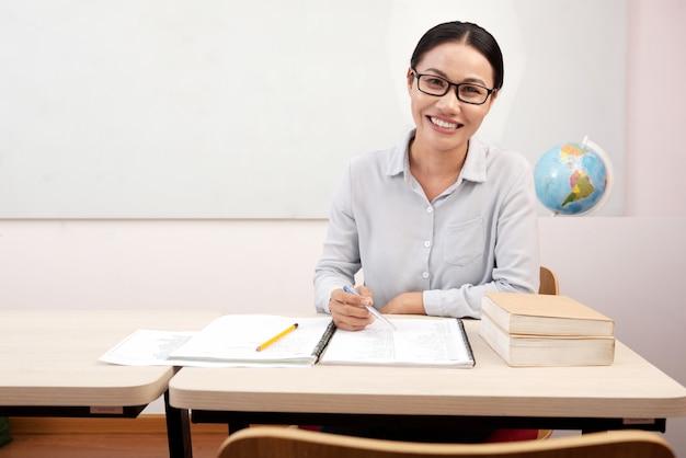 Profesor asiático femenino sonriente que se sienta en el escritorio en sala de clase y que escribe en cuaderno Foto gratis