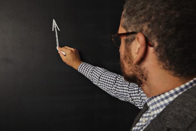 Profesor barbudo joven atractivo que comienza a dibujar un gráfico en la pizarra Foto gratis