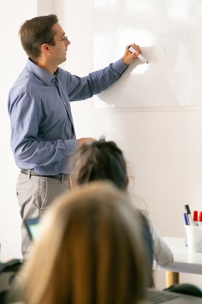 Profesor concentrado dibujando a bordo y explicando la lección a los alumnos Foto gratis