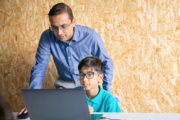 Profesor de contenido de mediana edad ayudando al niño con la lección y explicando el tema Foto gratis