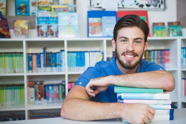 Profesor de la escuela sentado con libros en la biblioteca Foto Premium
