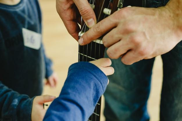 Profesor de guitarra que indica a un niño pequeño estudiante la colocación de los dedos en el mástil. Foto Premium