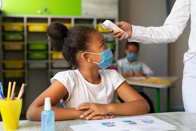 Profesor de lado tomando la temperatura de un alumno Foto gratis