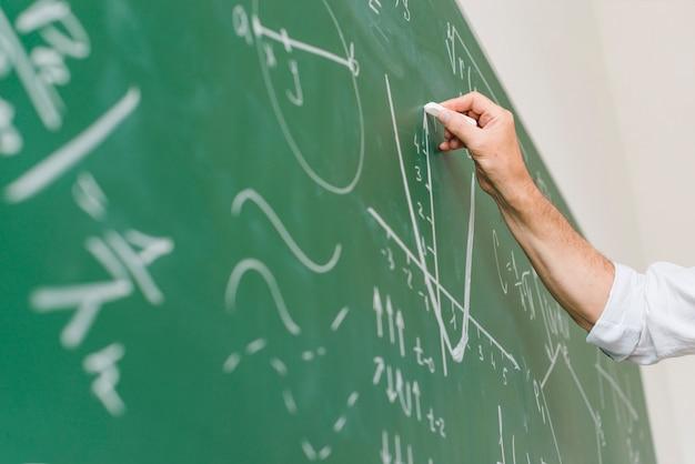 Profesor de matemáticas envejecido dibujando diagrama en pizarra Foto gratis