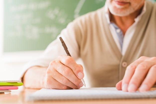 Profesor de matemáticas envejecido escribiendo en el cuaderno Foto gratis