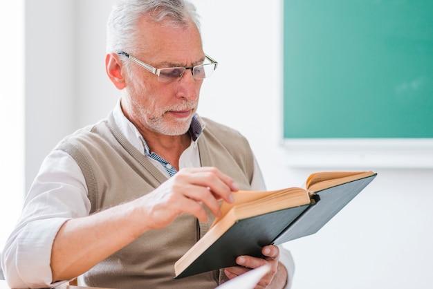 Profesor mayor leyendo un libro sentado en el aula Foto gratis