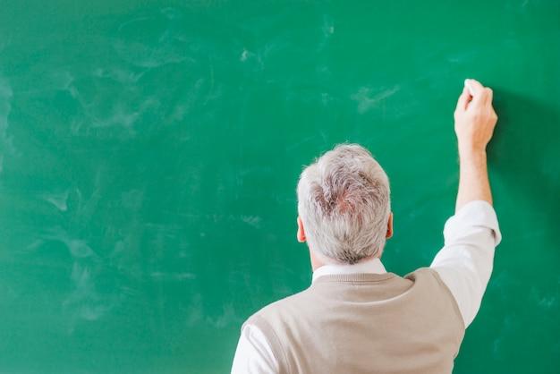 Profesor mayor que escribe en el tablero verde con tiza Foto gratis
