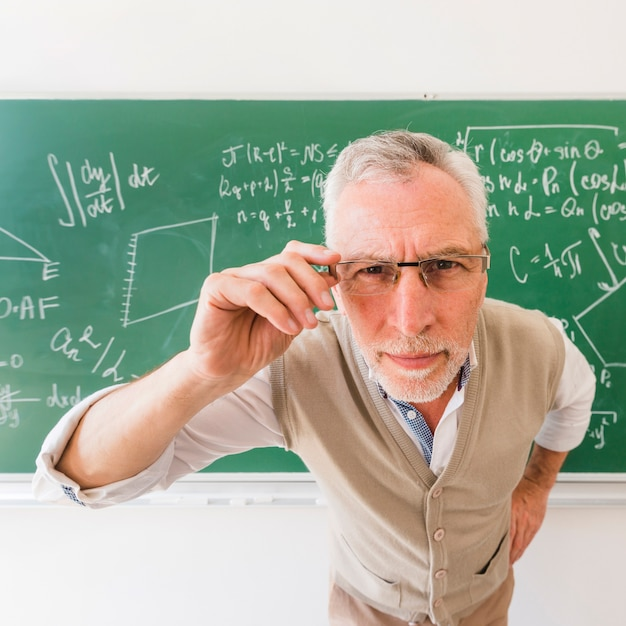 Profesor mayor que mira a través de los vidrios en la cámara Foto gratis