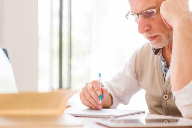Profesor mayor en vidrios que escribe en el cuaderno en sala de clase Foto gratis