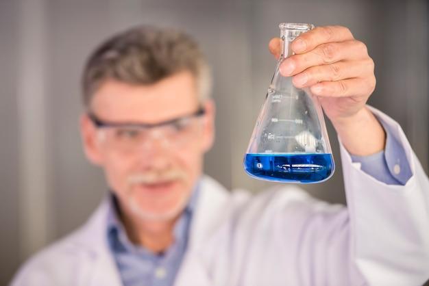 Profesor de química senior sosteniendo frasco con líquido azul. Foto Premium