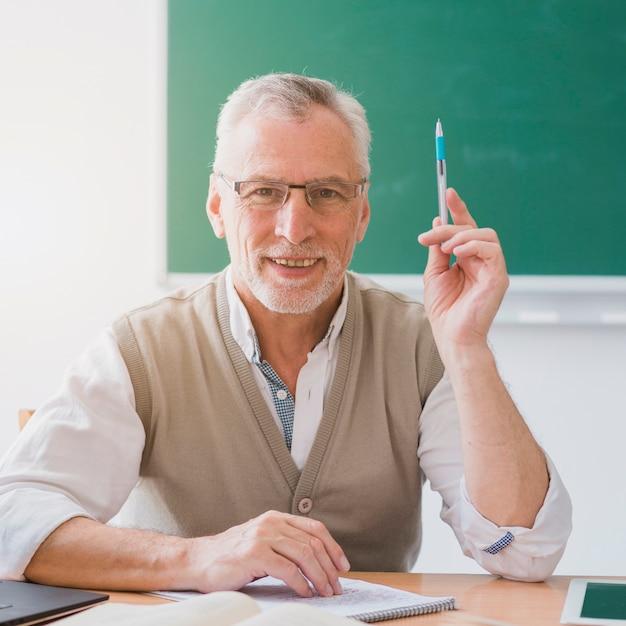 Profesor senior con la mano levantada sosteniendo la pluma en el aula Foto gratis