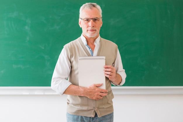 Profesor de sexo masculino mayor que sostiene el cuaderno que se opone a la pizarra Foto gratis