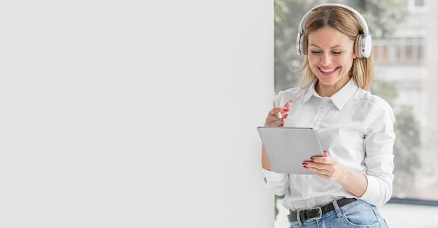 Profesor sonriente haciendo sus clases en una tableta con espacio de copia Foto Premium