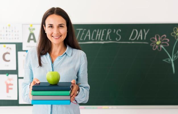 Profesor sonriente sosteniendo un montón de libros y una manzana con espacio de copia Foto gratis