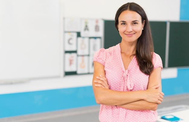Profesor sonriente sosteniendo sus brazos cruzados Foto gratis