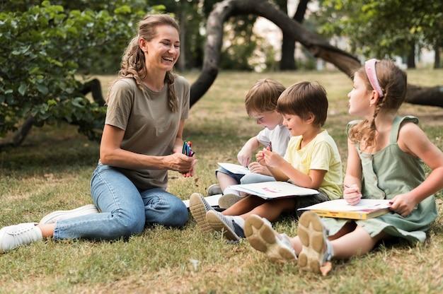 Profesor sonriente de tiro completo y niños al aire libre Foto gratis