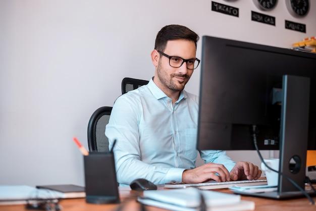 Programador encantado con gafas utilizando una computadora. Foto Premium
