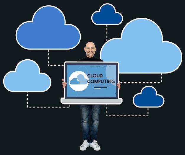 Programador sosteniendo una laptop con cloud computing. Foto gratis